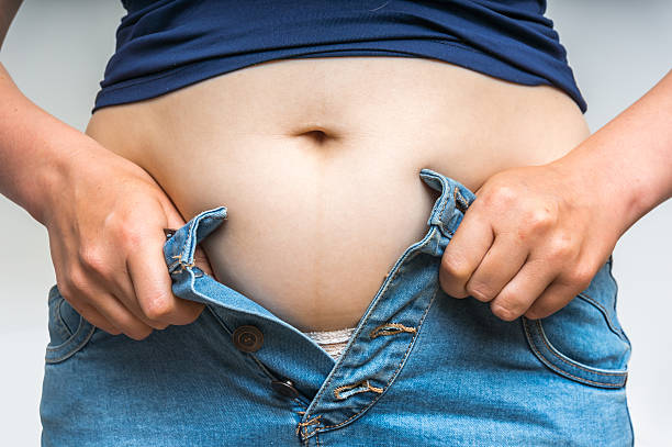 Overweight woman getting dressed wearing jeans - obesity concept